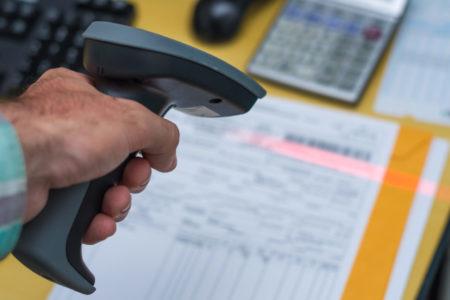 Ótimo conceito de rastreabilidade, sistema ERP, mão de homem escaneando código de barras de nota fiscal para pagamento