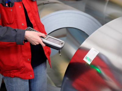 A worker has scanned steel roll production